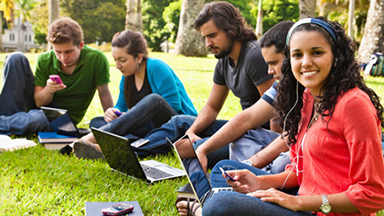 Students sitting in the grass working on computers